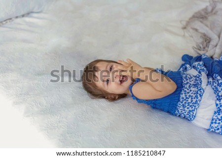 Funny and cute brunette little smiling girl playing jumping on bed in light bedroom. White interior with big bed. Childhood, preschool, youth, relax concept #1185210847