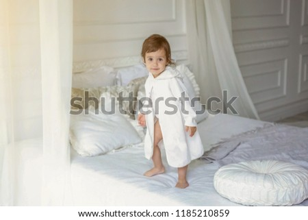 Funny and cute brunette little smiling girl playing jumping on bed in light bedroom. White interior with big bed. Childhood, preschool, youth, relax concept #1185210859