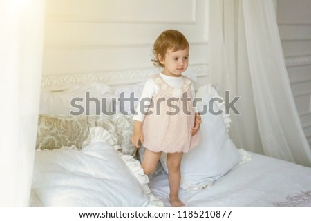 Funny and cute brunette little smiling girl playing jumping on bed in light bedroom. White interior with big bed. Childhood, preschool, youth, relax concept #1185210877