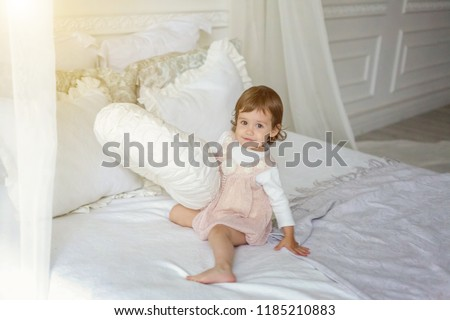 Funny and cute brunette little smiling girl playing jumping on bed in light bedroom. White interior with big bed. Childhood, preschool, youth, relax concept #1185210883