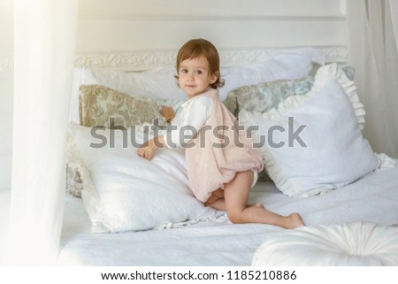 Funny and cute brunette little smiling girl playing jumping on bed in light bedroom. White interior with big bed. Childhood, preschool, youth, relax concept #1185210886