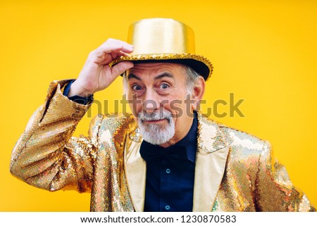 Funny and extravagant senior man posing on colored background - Youthful old man in the sixties having fun and partying #1230870583
