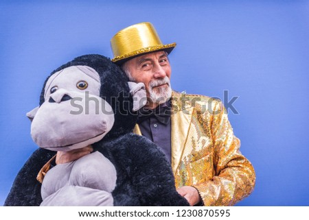 Funny and extravagant senior man posing on colored background - Youthful old man in the sixties having fun and partying #1230870595