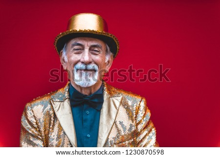 Funny and extravagant senior man posing on colored background - Youthful old man in the sixties having fun and partying #1230870598