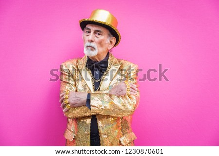 Funny and extravagant senior man posing on colored background - Youthful old man in the sixties having fun and partying #1230870601