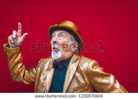 Funny and extravagant senior man posing on colored background - Youthful old man in the sixties having fun and partying #1230870604