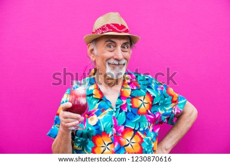 Funny and extravagant senior man posing on colored background - Youthful old man in the sixties having fun and partying #1230870616