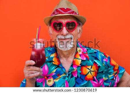 Funny and extravagant senior man posing on colored background - Youthful old man in the sixties having fun and partying #1230870619