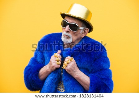 Funny and extravagant senior man posing on colored background - Youthful old man in the sixties having fun and partying Сток-фото ©