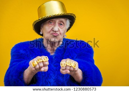 Funny and extravagant senior woman posing on colored background - Youthful old woman in the sixties having fun and partying #1230880573