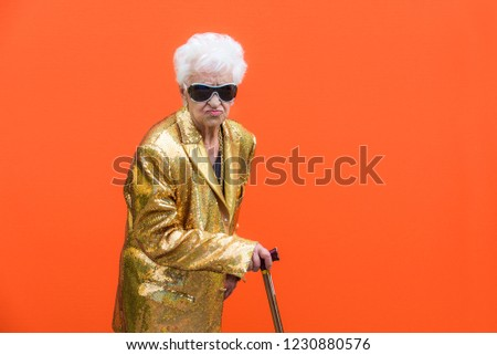 Funny and extravagant senior woman posing on colored background - Youthful old woman in the sixties having fun and partying #1230880576
