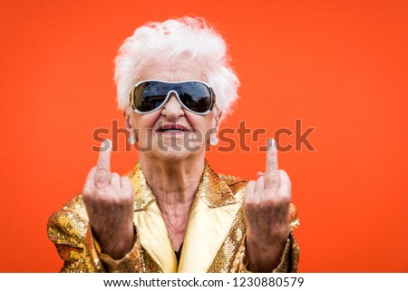 Funny and extravagant senior woman posing on colored background - Youthful old woman in the sixties having fun and partying