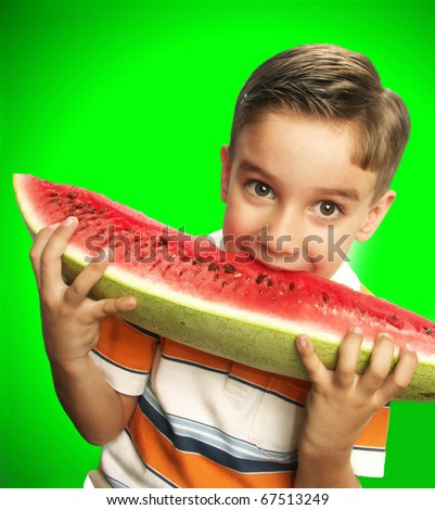 Funny and happy little boy eating watermelon.Little boy holding a big watermelon.