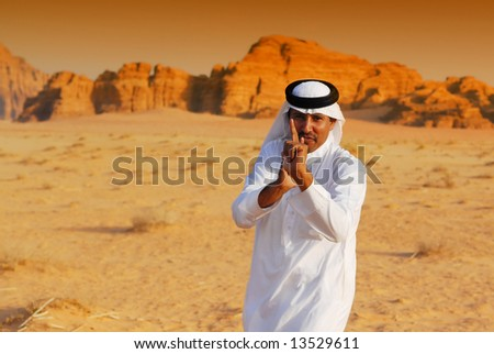 Funny arabic man playing terrorist by point and shoot with his hands in Wadi Rum desert at sunset, Jordan