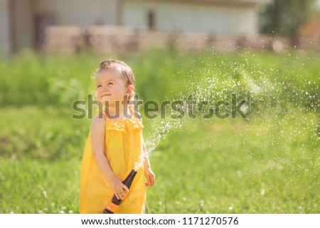 Funny babe watering the water from a hose in the garden
