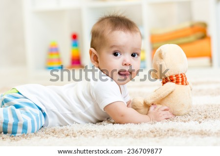 funny baby boy lying with plush toy indoor
