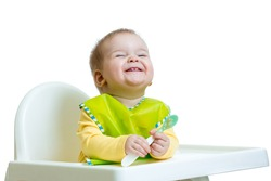 funny baby child sitting in chair with spoon isolated