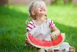 Funny baby eating watermelon outdoors in the park. Baby, baby, healthy food