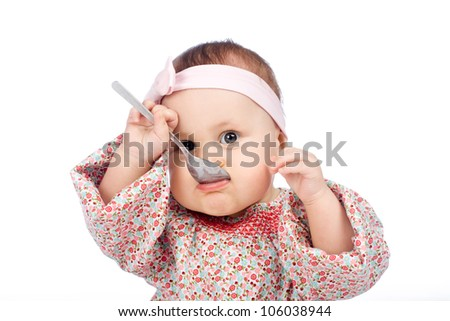 Funny baby girl eating with spoon, isolated over white
