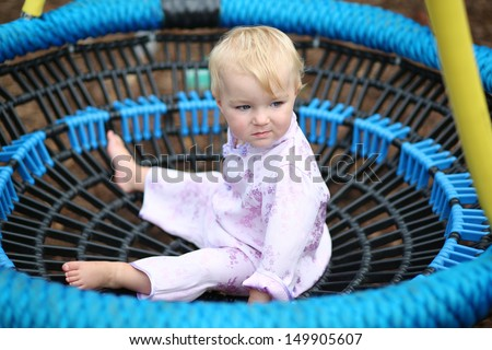 Funny baby girl in a beautiful kimono suit plays on a rubber net swing at a playground in the park