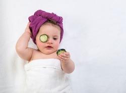 Funny, baby girl in purple bath turban looking at cucumber eye mask