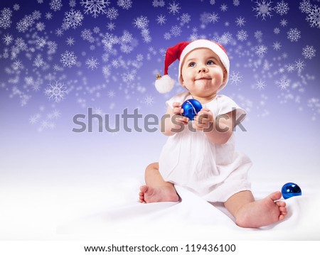 Funny baby girl in santa's hat over dark blue background with snowflakes
