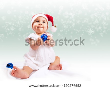Funny baby girl in santa's hat over light background with snowflakes