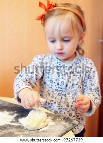Funny baby girl knead the dough