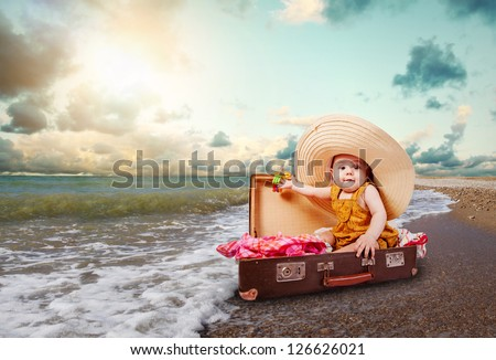 Funny baby girl traveler sitting in retro suitcase at the sea coast