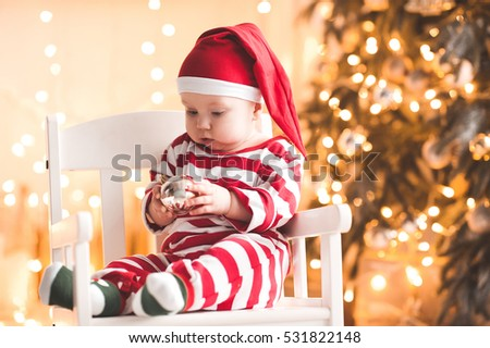Stock Photo Funny baby girl wearing santa claus hat and suit playing with Christmas ball over Christmas tree in room. Holiday season.