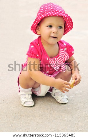 funny baby girl wearing spotted clothing eating cakes outdoors
