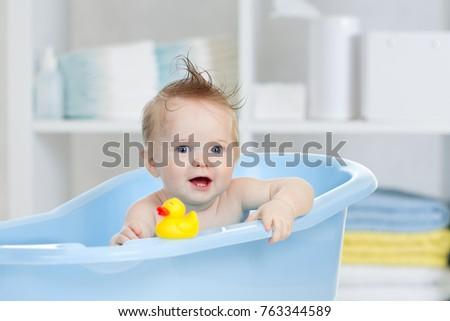 Funny baby having bath in blue tub
