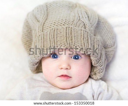 Funny baby in a huge knitted hat wearing a warm sweater relaxing on a white blanket