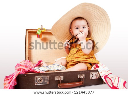 Funny baby in big summer hat girl sitting into old suitcase