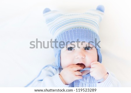 Funny baby playing with its hat