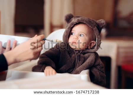 Funny Baby Sitting in Highchair Refusing to Eat. Small infant being a picky eater disliking the food