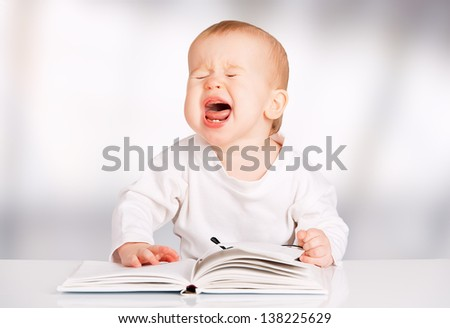 funny baby with glasses reading a book and cries