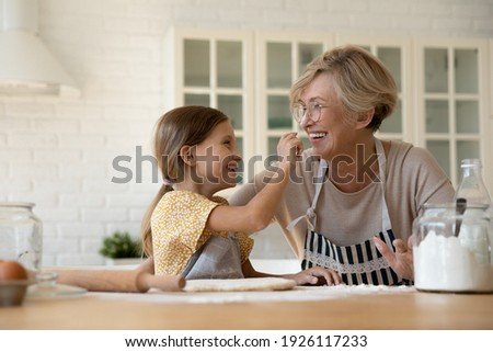 Funny baking. Joyful little girl having fun with retired older grandma when cooking pastries. Laughing elderly granny and cute small grandchild playing at kitchen painting one another noses with flour