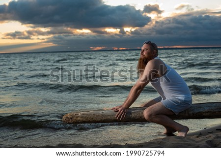 Funny bald man with red beard posing on the beach at sunset. A humorous male parody of a glamorous girl. Stock photo ©