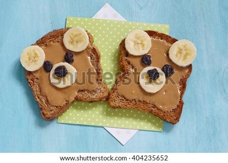 Funny bear face sandwich with peanut butter, banana and raisins