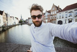 Funny bearded hipster taking selfie portrait in Bruges old town, Belgium. Handsome male blogger takes photo for social media.