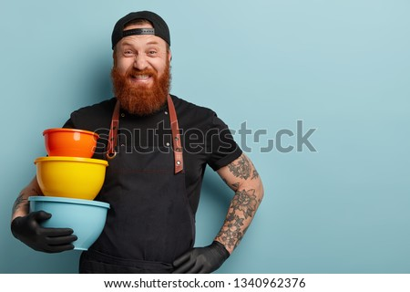Funny bearded man clenches teeth, has cheerful expression, holds colourful utensils of different size, wears black headgear and apron, isolated in blue studio wall with empty space for information