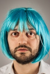 Funny bearded man with a blue wig on grey background