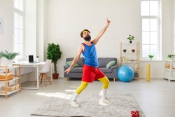 Funny bearded young man in colorful retro sportswear doing fitness exercise, dancing and fooling around in his living-room during sport workout at home