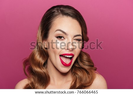 Stock Photo Funny beautiful brunette lady winking and smiling isolated while looking camera isolated