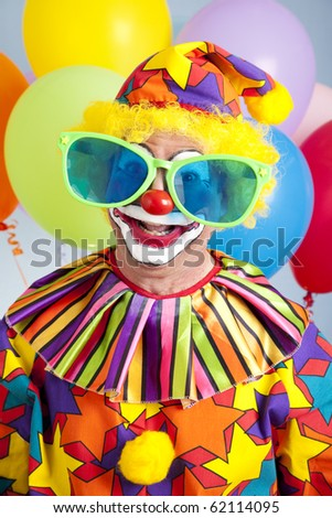 Funny birthday clown wearing over-sized novelty sunglasses.