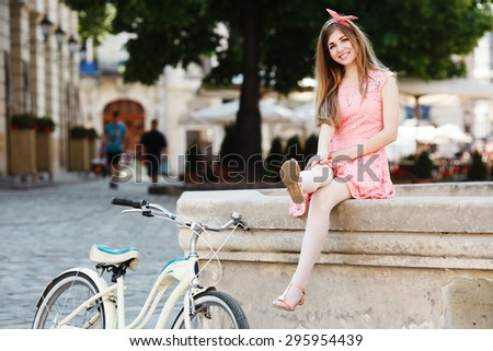 Funny blond-brown girl having fun with her feet. Wearing pink head wrap and dress with a pattern of flowers. Looking at camera. With retro bicycle nearby. In the old European city.