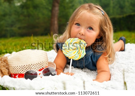 Funny blond toddler girl with lollipop lying on white plaid