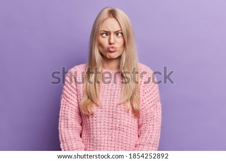 Funny blonde young woman has silly grimace crosses eyes and pouts lips makes brainless face wears knitted sweater isolated over purple background foolishes around. Human face expressions concept Stock photo ©