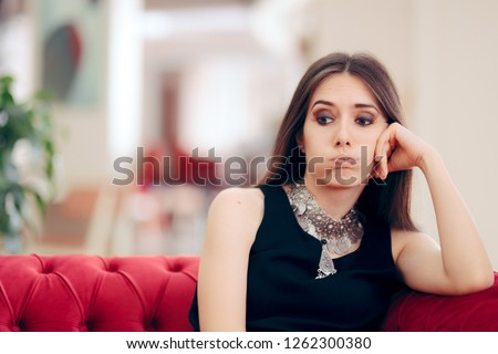 Funny Bored Elegant Woman Waiting in Hotel Lobby. Unhappy stood-up girl tired of waiting on a couch